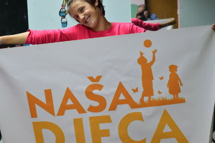 Beneficiary of Our Kids Foundation projects, Mostar, holding a banner.