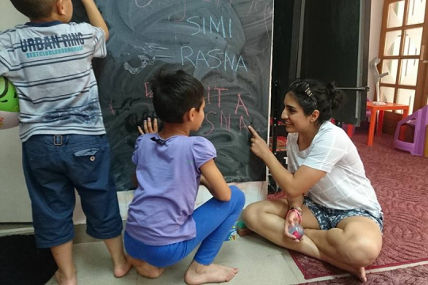Our Kids Foundation volunteer writing at blackboard with children at Children's Home Mostar.