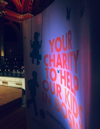 """""""Your Charity to Help Our Kids in Bosnia"""". Promotional banner at Our Kids Foundation fundraising concert."""