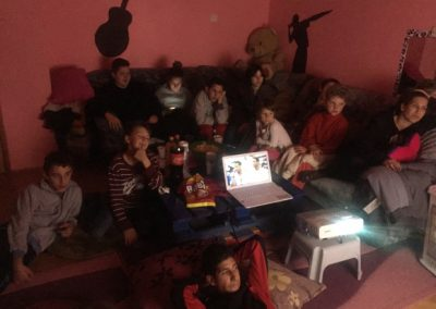 Children from Children's Home Mostar, watching a movie on laptop donated by HERO World Support.