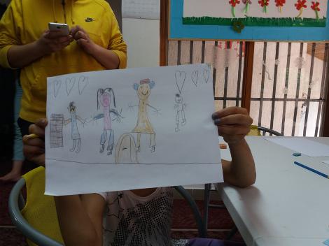 Child showing a drawing, at Egipatsko Selo children's home Mostar
